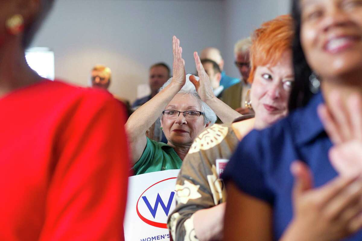 Pat Burnham, 63, center, who became an electrician so she could earn equal pay, joined the crowd Tuesday at The Woman's Home in Houston to lobby for equal pay for women.