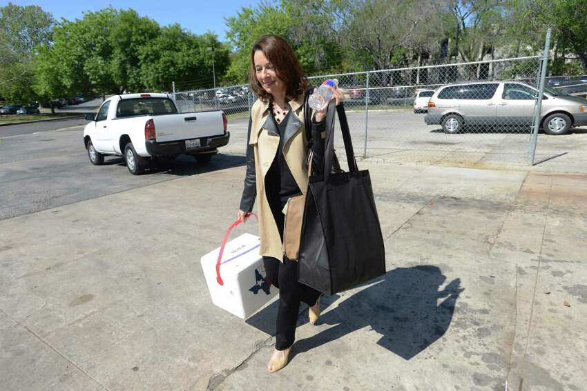 Elder law attorney Carmen Samaniego carries food for delivery to seniors on Tuesday, April 8, 2014. She and other female executives in San Antonio delivered meals to homebound seniors on behalf of Christian Senior Services during the