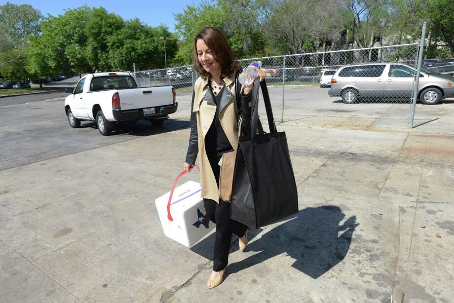 "Elder law attorney Carmen Samaniego carries food for delivery to seniors on Tuesday, April 8, 2014. She and other female executives in San Antonio delivered meals to homebound seniors on behalf of Christian Senior Services during the ""Hot Meals on High Heels"" event. Photo: Billy Calzada, San Antonio Express-News / San Antonio Express-News"