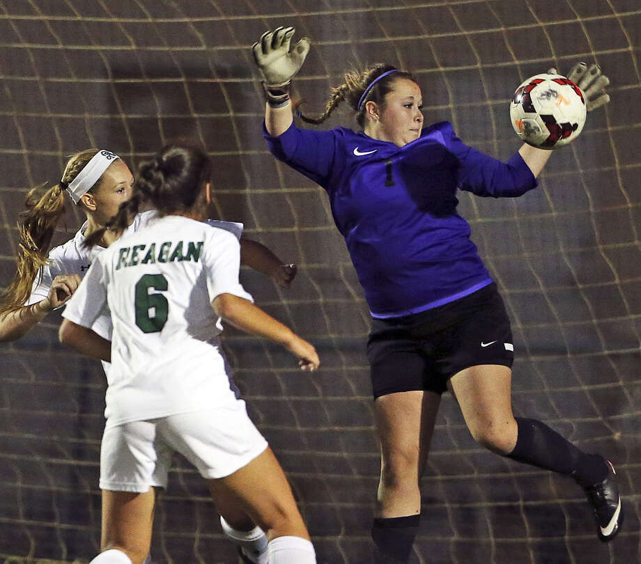 Steele goalie Victoria Simpson (right) stops a shot in front of a pair of Reagan players  during a Region IV-5A quarterfinal match at Blossom Stadium on Tuesday. Photo: Tom Reel / San Antonio Express-News
