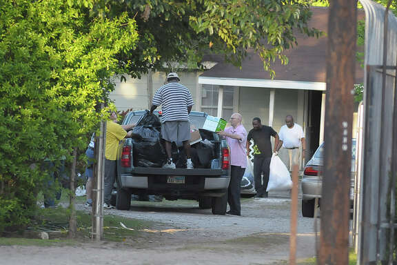 Residents are assisted in moving out of their halfway house at 9330 West Montgomery Road on Tuesday.