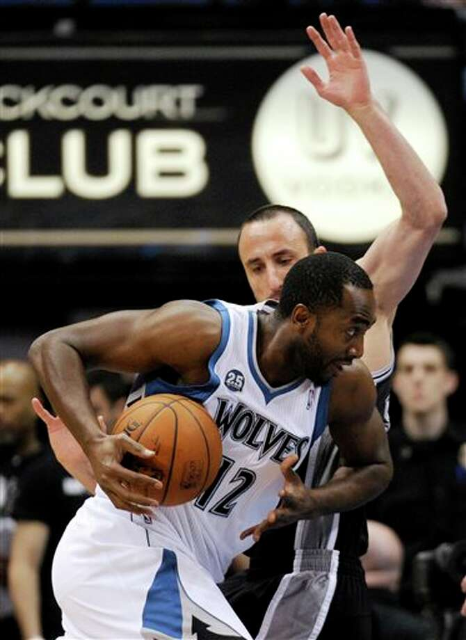 Minnesota Timberwolves' Luc Richard Mbah a Moute (12), from Cameroon, drives against San Antonio Spurs guard Manu Ginobili, from Argentina, during the first quarter in an NBA basketball game at the Target Center on in Minneapolis on Tuesday, April 8, 2014. (AP Photo/Hannah Foslien) Photo: Hannah Foslien, AP / FR159563 AP