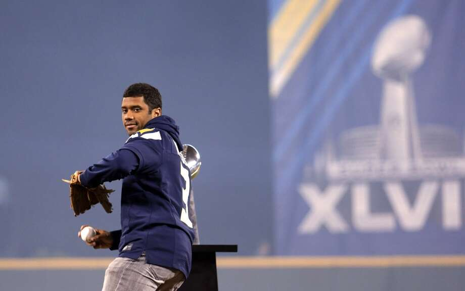 2014  First pitch: Quarterback Russell Wilson, joined by other members of the Super Bowl-champion Seahawks including Pete Carroll, Malcolm Smith, Jermaine Kearse, K.J. Wright, Zach Miller, Mike Morgan and Bobby Wagner  National Anthem: Navy Band Northwest Photo: Elaine Thompson, Associated Press