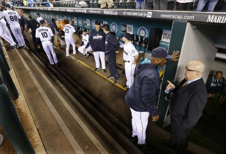 Seattle Mariners general manager Jack Zduriencik, right, talks with new manager Lloyd McClendon, second from right, in the dugout Tuesday, April 8, 2014, just before the Mariners' home-opener baseball game against the Los Angeles Angels in Seattle. (AP Photo/Ted S. Warren) Photo: Ted S. Warren, AP