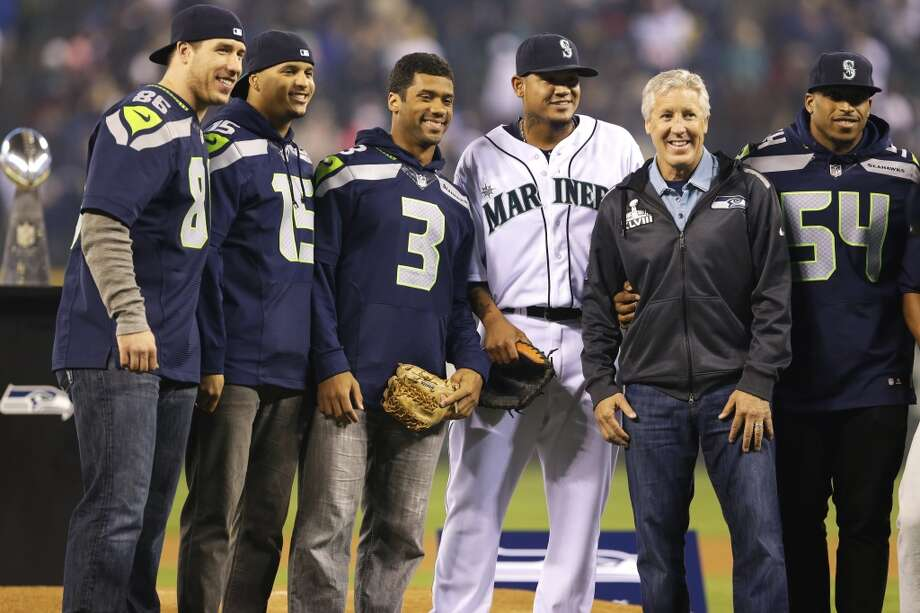 Seattle Mariners starting pitcher Felix Hernandez, third from right, poses for a photo with Seattle Seahawks, from left, Zach Miller, Jermaine Kearse, Russell Wilson, coach Pete Carroll, and Bobby Wagner after Wilson threw out the ceremonial first pitch, Tuesday, April 8, 2014, before the Mariners' home-opener baseball game against the Los Angeles Angels in Seattle. (AP Photo/Ted S. Warren) Photo: Ted S. Warren, AP