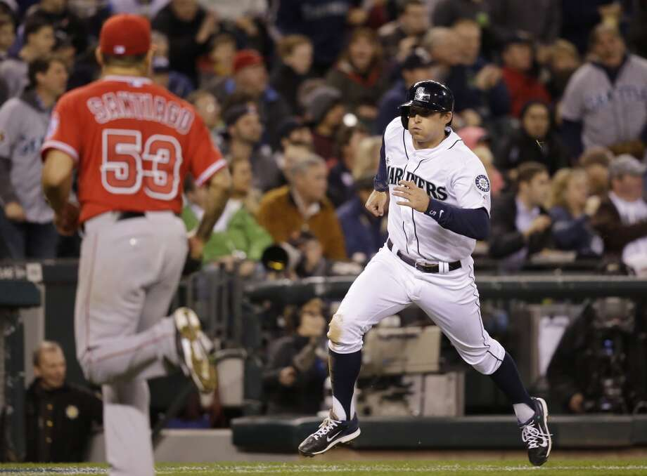 Seattle Mariners' Brad Miller, right, races in to score as Los Angeles Angels starting pitcher Hector Santiago heads home to back up the play during the third inning of a baseball game Tuesday, April 8, 2014, in Seattle. (AP Photo/Elaine Thompson) Photo: Elaine Thompson, AP