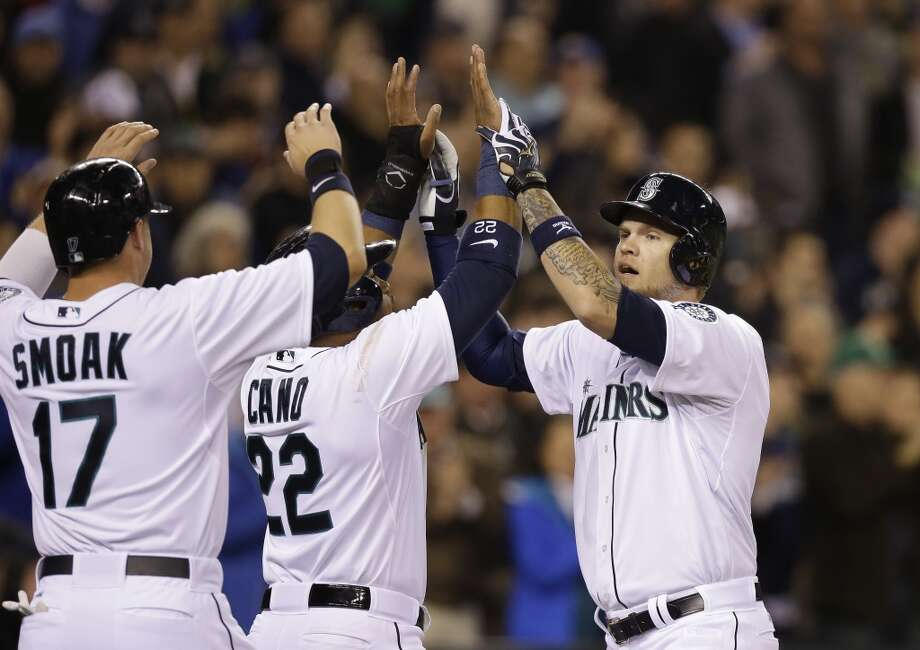 Seattle Mariners' Corey Hart, right, is greeted at home by Justin Smoak (17) and Robinson Cano on his three-run home run against the Los Angeles Angels in the third inning of a baseball game Tuesday, April 8, 2014, in Seattle. (AP Photo/Elaine Thompson) Photo: Elaine Thompson, AP