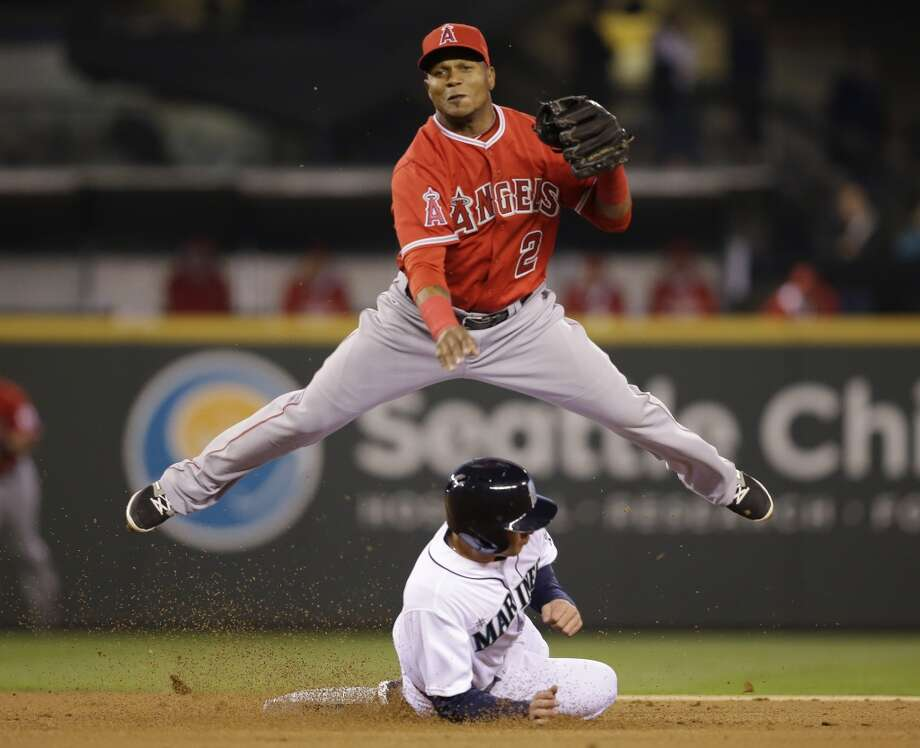 Los Angeles Angels shortstop Erick Aybar leaps out of the way after forcing out Seattle Mariners' Brad Miller at second base and throwing to first to complete the double play in the first inning of a baseball game Tuesday, April 8, 2014, in Seattle. Robinson Cano was out at first. (AP Photo/Elaine Thompson) Photo: Elaine Thompson, AP