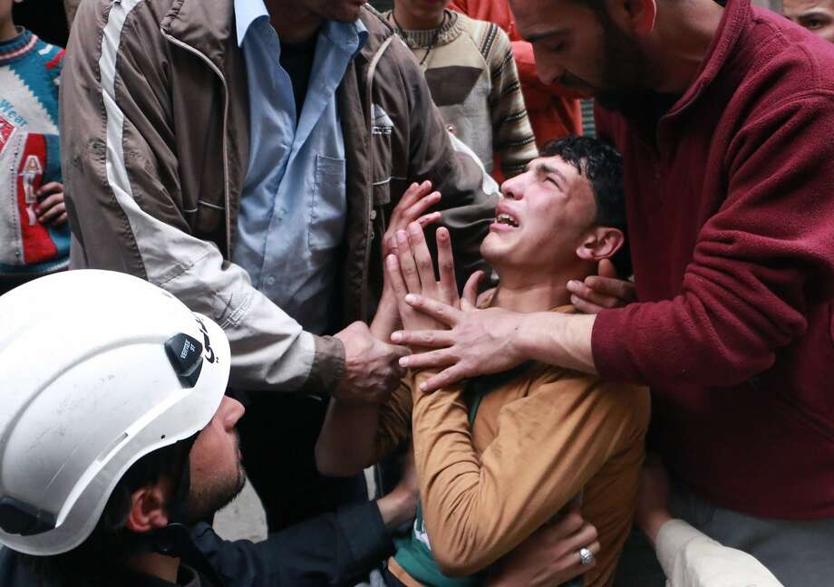 TOPSHOTS A man is comforted by a rescue worker and others following a reported air strike by government forces in which a fellow rescue worker was killed on March 8, 2014 in the northern city of Aleppo. More than 140,000 people have been killed in Syria since the start of a March 2011 uprising against the Assad family's 40-year rule. AFP PHOTO / AMC / FADI AL-HALABIFadi al-Halabi/AFP/Getty Images Photo: Fadi Al-halabi, AFP/Getty Images