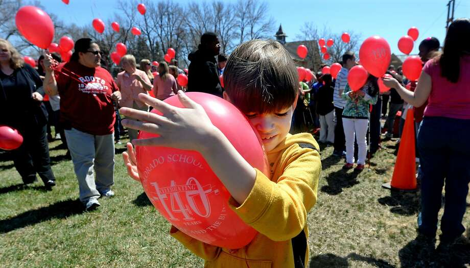 Phoenix Garcia, a student with vision loss, uses his hands and face to feel the balloon before he turns it loose during a celebratory balloon launch Tuesday, April 8, 2014, in Colorado Springs, Colo. Students, staff and alumnae from the Colorado School for the Deaf and the Blind celebrated 140 years of existence. (AP Photo/The Colorado Springs Gazette, Jerilee Bennett) Photo: Jerilee Bennett, Associated Press