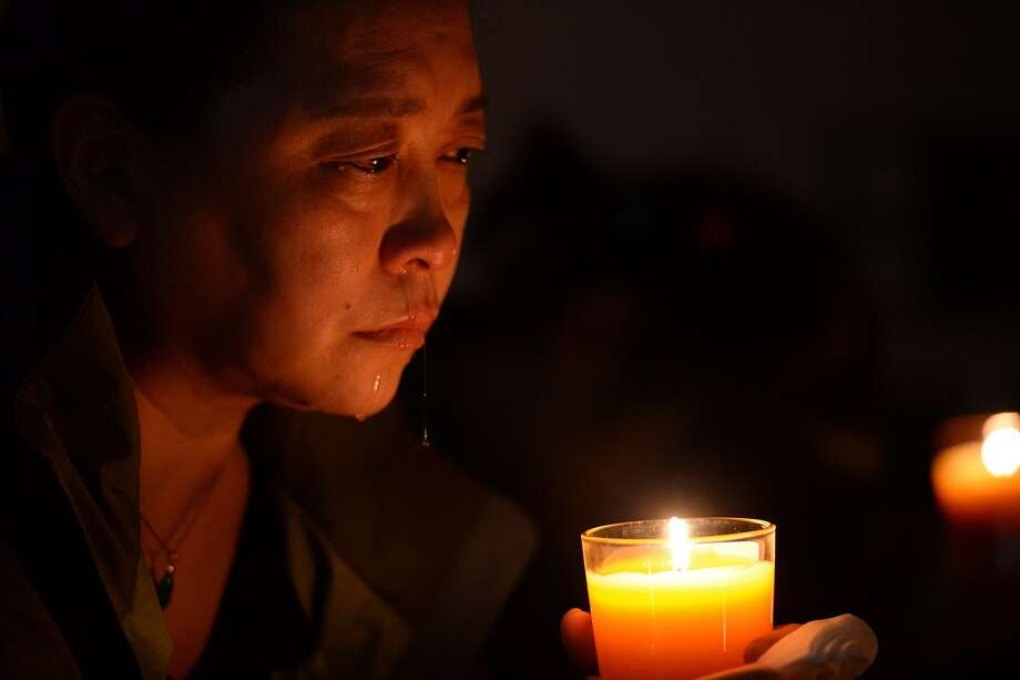 TOPSHOTS A Chinese relative of passengers on the missing Malaysia Airlines flight MH370 cries as she prays at the vigil in the Metro Park Hotel in Beijing on April 8, 2014. Family members of passengers on board Malaysia Airlines flight MH370 held a tearful vigil in Beijing in the early hours of April 8 to mark one month since contact with the plane was lost.  CHINA OUT     AFP PHOTOSTR/AFP/Getty Images Photo: Str, AFP/Getty Images