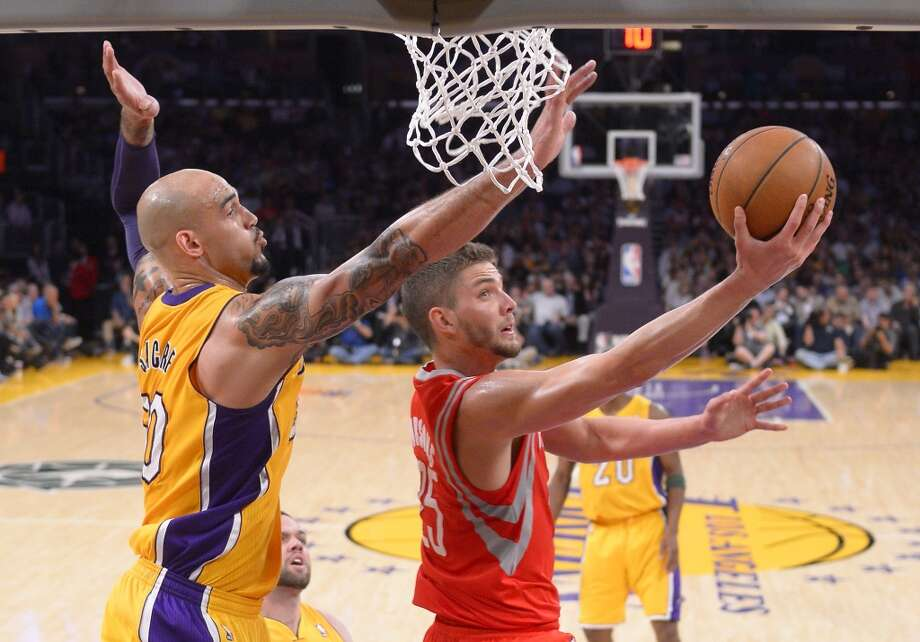 Rockets forward Chandler Parsons attempts a basket against Robert Sacre of the Lakers. Photo: Mark J. Terrill, Associated Press
