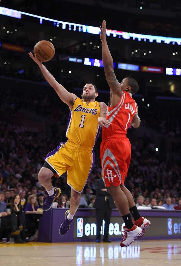 Lakers guard Jordan Farmar attempts a basket against Isaiah Canaan of the Rockets. Photo: Mark J. Terrill, Associated Press