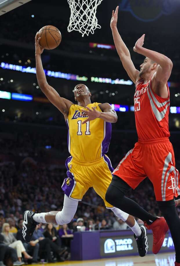 Wesley Johnson of the Lakers attempts to shoot over Rockets forward Chandler Parsons. Photo: Mark J. Terrill, Associated Press