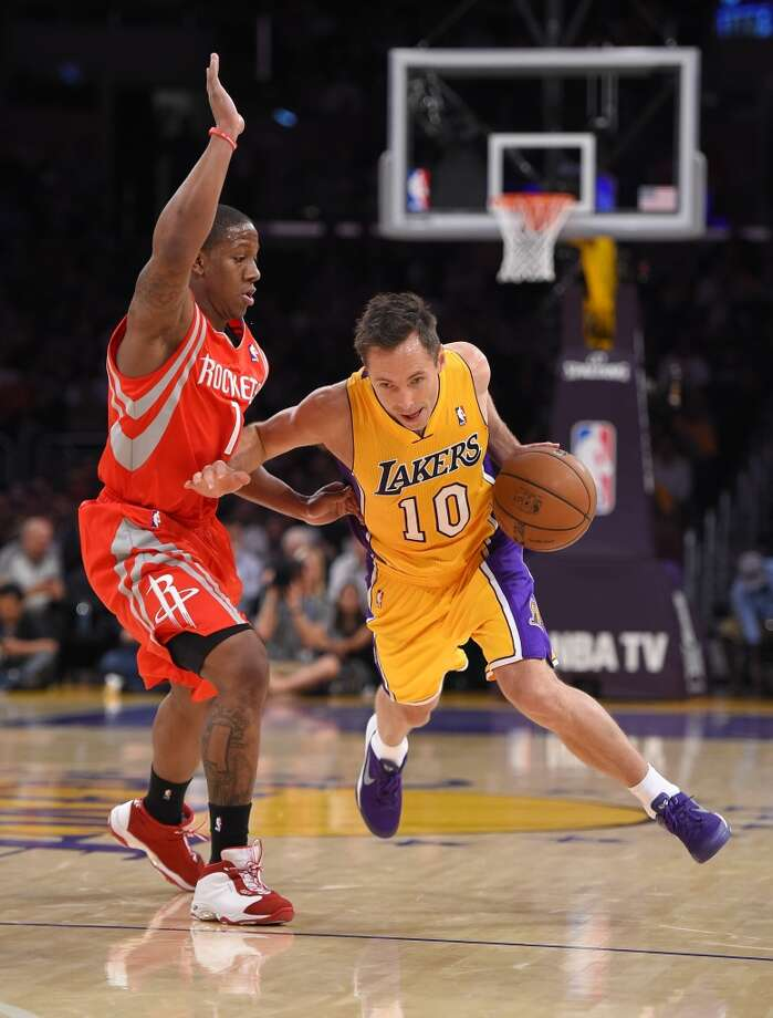 Steve Nash of the Lakers tries to drive past Rockets guard Isaiah Canaan. Photo: Mark J. Terrill, Associated Press