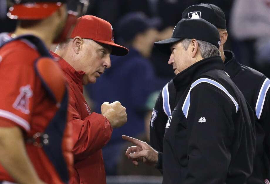 Los Angeles Angels manager Mike Scioscia, left, talks with umpire Mike Winters after the Seattle Mariners won a challenge with a video review in the fifth inning of a baseball game Tuesday, April 8, 2014, in Seattle. (AP Photo/Elaine Thompson) Photo: Elaine Thompson, AP