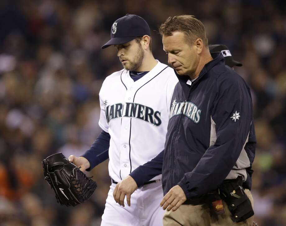 Seattle Mariners starting pitcher James Paxton, left, is accompanied by a trainer as he leaves the baseball game against the Los Angeles Angels in the sixth inning Tuesday, April 8, 2014, in Seattle. Paxton strained a muscled in his left side, the team said. (AP Photo/Elaine Thompson) Photo: Elaine Thompson, AP