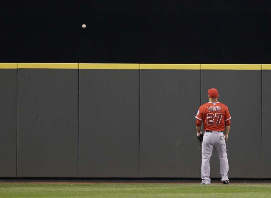 Los Angeles Angels center fielder Mike Trout can only watch as a solo home run hit by Seattle Mariners' Corey Hart goes over the wall in the seventh inning of a baseball game, Tuesday, April 8, 2014, in Seattle. It was Hart's second home run of the game. (AP Photo/Ted S. Warren) Photo: Ted S. Warren, AP