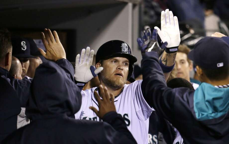 Seattle Mariners' Corey Hart is congratulated in the dugout after hitting a home run against the Los Angeles Angels in the seventh inning of a baseball game Tuesday, April 8, 2014, in Seattle. (AP Photo/Elaine Thompson) Photo: Elaine Thompson, AP