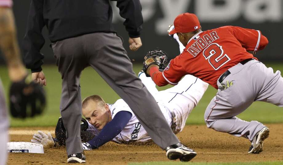 Seattle Mariners' Kyle Seager is safe at second with a double ahead of the tag attempt by Los Angeles Angels shortstop Erick Aybar (2) in the third inning of a baseball game, Tuesday, April 8, 2014, in Seattle. (AP Photo/Ted S. Warren) Photo: Ted S. Warren, AP