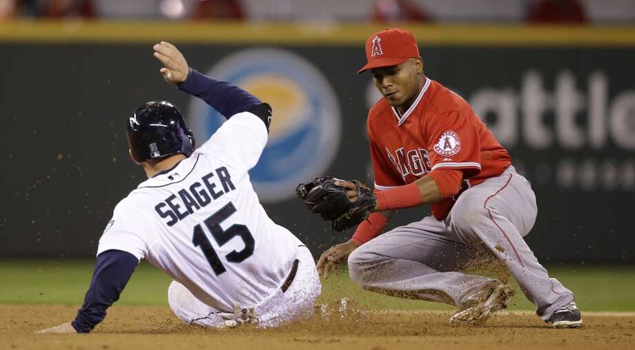 Seattle Mariners' Kyle Seager (15) slides into a tag by Los Angeles Angels shortstop Erick Aybar and is out on an attempted steal in the seventh inning of a baseball game Tuesday, April 8, 2014, in Seattle. (AP Photo/Elaine Thompson) Photo: Elaine Thompson, AP