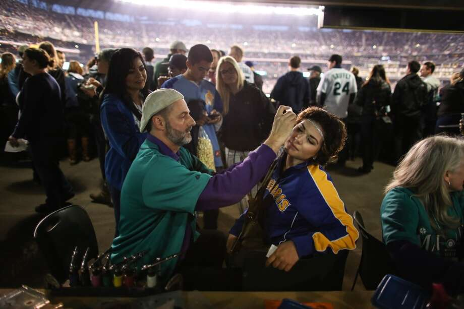 Meshelle Anderson has her face painted by Mark Wilson, an artist with Merry Makers, during the Seattle Mariners home opener on Tuesday, April 8, 2014 at Safeco Field. The Mariners defeated the Los Angeles Angels 5-3. (Joshua Trujillo, seattlepi.com) Photo: JOSHUA TRUJILLO, SEATTLEPI.COM