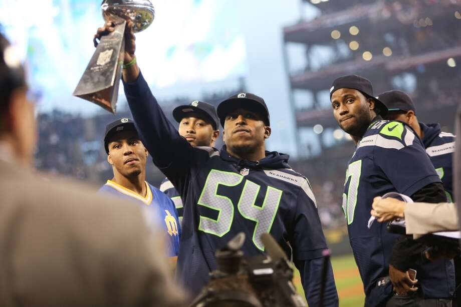 Seattle Seahawks player Bobby Wagner hoists the Lombardi Trophy during the Seattle Mariners home opener on Tuesday, April 8, 2014 at Safeco Field. The Mariners defeated the Los Angeles Angels 5-3. (Joshua Trujillo, seattlepi.com) Photo: JOSHUA TRUJILLO, SEATTLEPI.COM