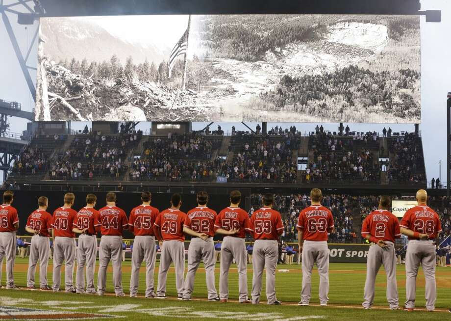 Los Angeles Angels stand on the baseline Tuesday, April 8, 2014, as photos of the deadly mudslide that struck the community of Oso, Wash., last month are shown during a moment of silence before the Seattle Mariners' home-opener baseball game against the Angels in Seattle. (AP Photo/Ted S. Warren) Photo: AP