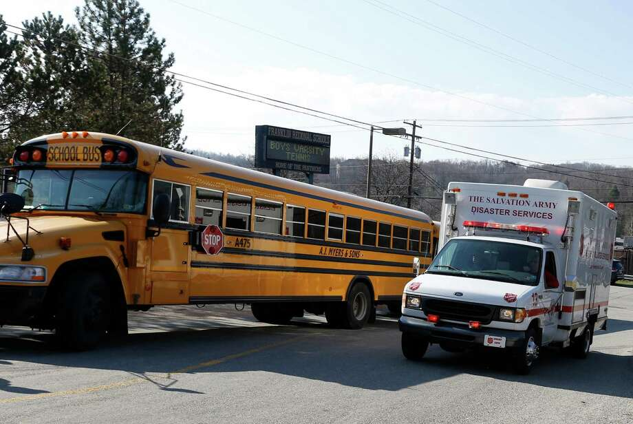 A Salvation Army disaster services vehicle drives past a school bus onto the campus of the Franklin Regional School District where several people were stabbed at Franklin Regional High School, Wednesday, April 9, 2014 in Murrysville, Pa., near Pittsburgh. The suspect, a male student, was taken into custody and being questioned. Photo: Keith Srakocic, AP / AP