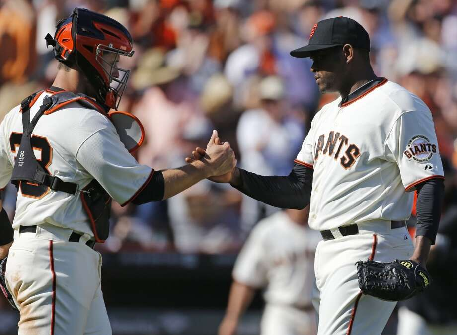 Giants pitcher Santiago Casilla, (46, right, ) closes out the ninth inning striking out Mark Trumbo, (15) and gets a handshake from cather Buster Posey, (28) as the San Francisco Giants beat the Arizona Diamondback 7-3, during their home opener at AT&T Park on Tuesday April 8, 2014, in San Francisco, Calif. Photo: The Chronicle