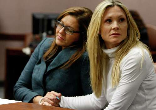 """Attorney Ellen Torregrossa-O'Connor, left, holds the hand of  former """"Melrose Place"""" actress Amy Locane-Bovenizer, 40, of Hopewell Township, N.J. as the jury in her trial returns a verdict on Tuesday, Nov. 27, 2012 in Somerville, N.J.   The jurors convicted Locane-Bovenizer of vehicular homicide, but acquitted her of a more serious charge, aggravated manslaughter, in the 2010 accident that killed a 60-year-old woman. Somerset County prosecutors said Locane-Bovenizer's blood-alcohol level was nearly three times the legal limit when the crash occurred on a dark two-lane road in Montgomery Township. The defence conceded she was driving under the influence. But her lawyer claimed a woman was chasing her after an earlier accident, forcing her to speed.  (AP Photo/The Star-Ledger, Robert Sciarrino, Pool) Photo: Robert Sciarrino"""