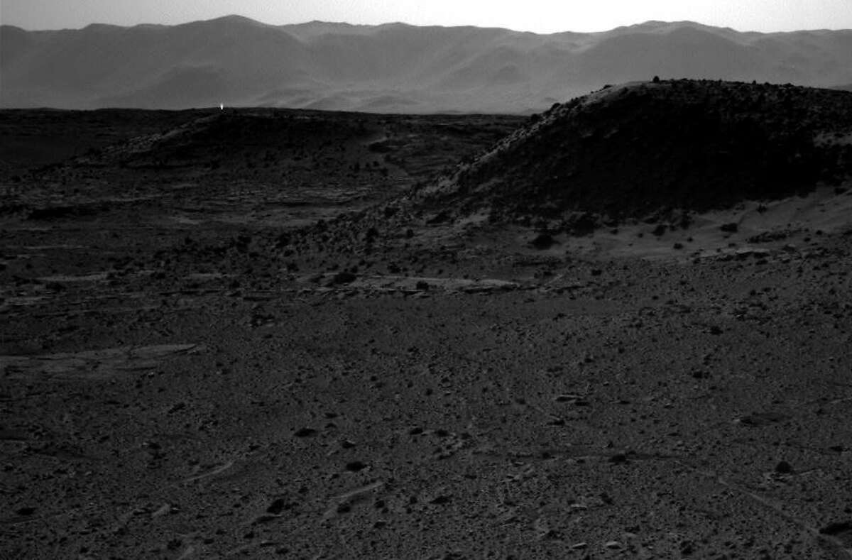 This image taken by NASA's Curiosity Mars rover's right-eye camera of the stereo Navcam on April 3, 2014 includes a bright spot, upper left, which might be due to the sun glinting off a rock or cosmic rays striking the camera's detector. Bright spots appear in images from the rover nearly every week. Typical explanations for them are cosmic rays hitting the light detector or sunlight glinting from rocks. (AP Photo/NASA)