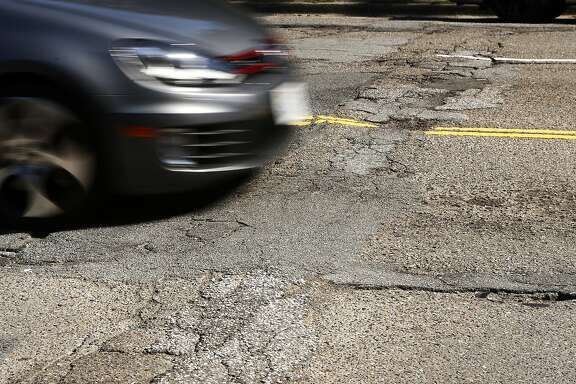 Cars drive down the pothole riddle Kezar Drive on Tuesday, April 8, 2014 in San Francisco, Calif.