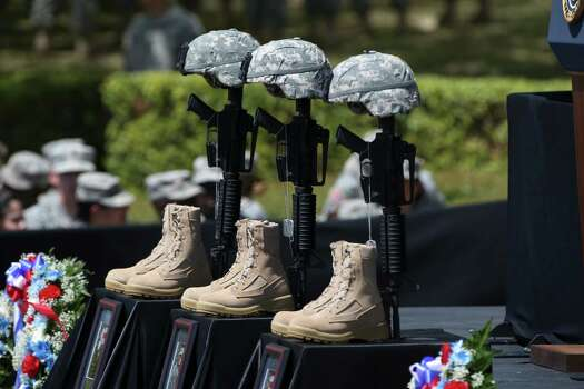 A memorial to three slain soldiers stands before a podium where President Barack Obama delivers remarks about the recent mass shooting carried out by Spc. Ivan A. Lopez at Fort Hood, Texas, April 9, 2014. Obama last visited the base in 2009 for a memorial for another mass shooting, carried out by Maj. Nidal Malik Hasan. Photo: DOUG MILLS, New York Times / NYTNS