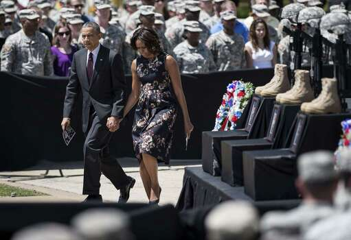 US President Barack Obama and First Lady Michelle Obama arrive for a memorial service at Fort Hood April 9, 2014 in Texas. US President Barack Obama attended a memorial service for the three people killed and 16 wounded during last weeks shooting at the post by Army Specialist Ivan Lopez who later took his own life.    AFP PHOTO/Brendan SMIALOWSKIBRENDAN SMIALOWSKI/AFP/Getty Images Photo: BRENDAN SMIALOWSKI, AFP/Getty Images / 2014 Brendan Smialowski