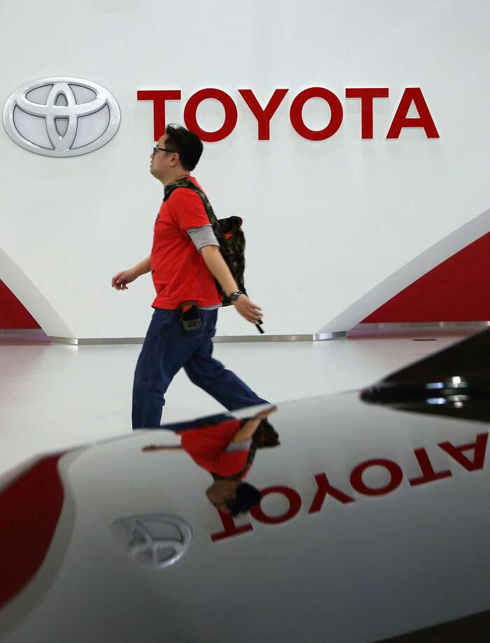 A visitor walks past the Toyota Motor Corp. logo displayed at the company's showroom in Tokyo, Japan, on Wednesday, April 9, 2014. Toyota, the world's largest carmaker, called back more than 6 million vehicles to fix a range of safety defects in one of the biggest recalls in automotive history. Photographer: Tomohiro Ohsumi/Bloomberg Photo: Tomohiro Ohsumi, Bloomberg