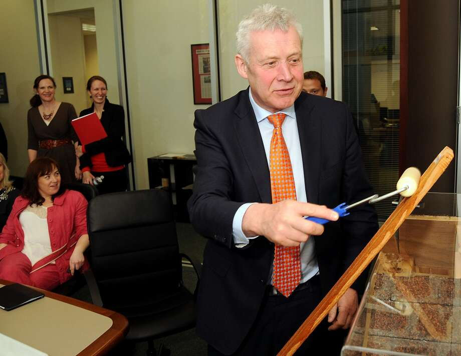 Ireland's Minister of State Fergus O'Dowd applies the C-Voltaics coating to a piece of wood during a tour at the University of Houston's Energy Research Park in April 2014. Photo: Dave Rossman, For The Houston Chronicle
