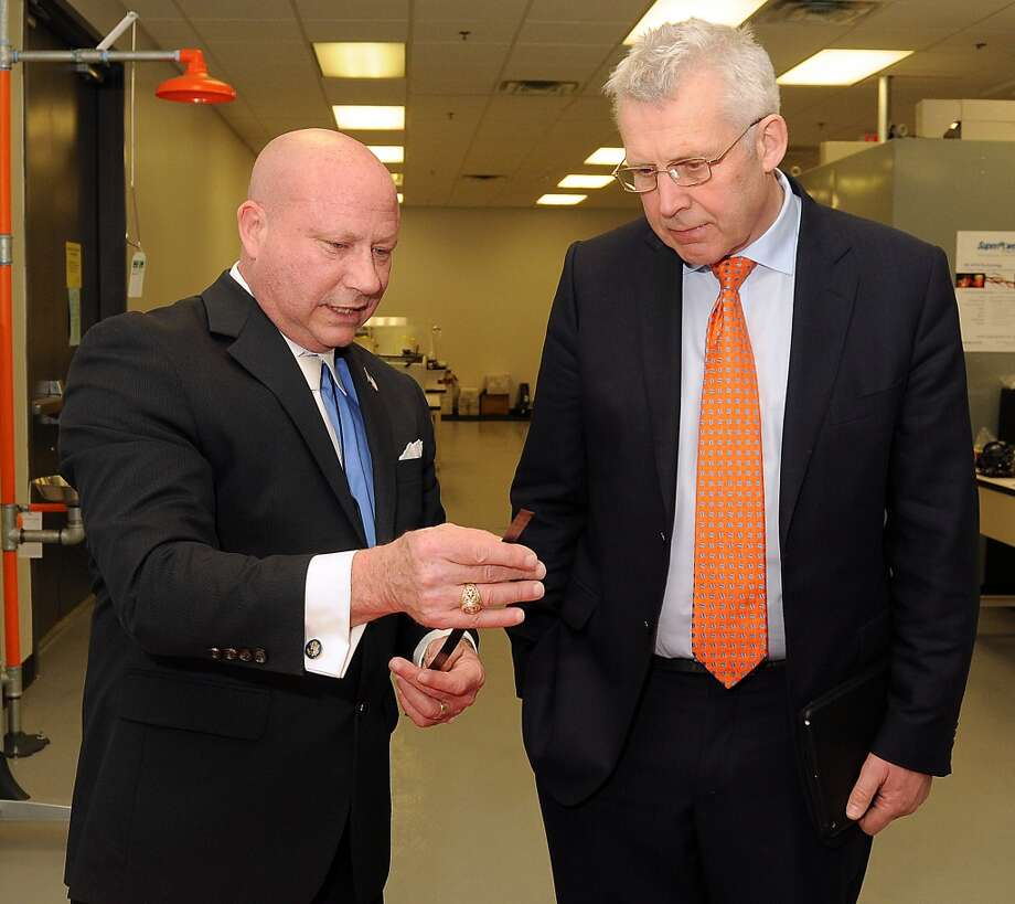 T. J. Wainerdi (left), University of Houston's Energy Research business director, shows Ireland's Minister of State Fergus O'Dowd a piece of superconducting wire at the University of Houston's Energy Research Park in April 2014. Photo: Dave Rossman, For The Houston Chronicle
