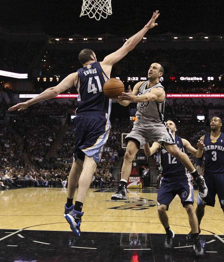 San Antonio Spurs' Manu Ginobili passes around Memphis Grizzlies' Kosta Koufos during the second half at the AT&T Center, Sunday, April 6, 2014. The Spurs won 112-92. Photo: Jerry Lara, San Antonio Express-News