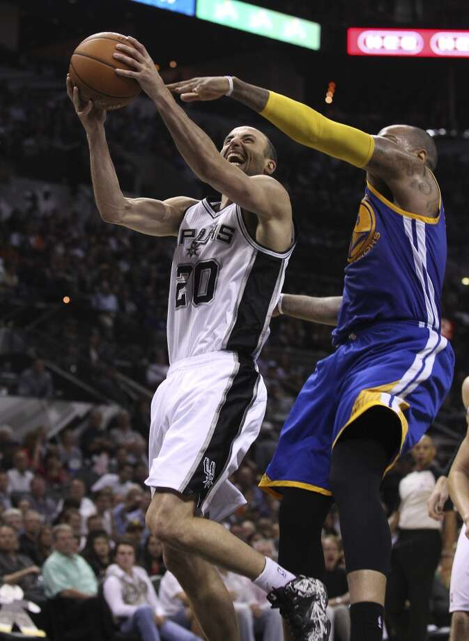 Spurs' Manu Ginobili (20) goes up for a shot against Golden State Warriors' Marreese Speights (05) in the second half at the AT&T Center on Wednesday, Apr. 2, 2014. Spurs defeated the Warriors, 111-90. Photo: Kin Man Hui, San Antonio Express-News