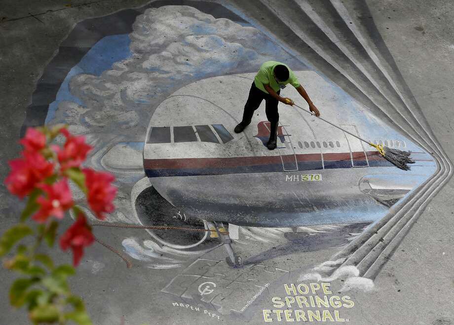 "A school utility worker mops a mural depicting the missing Malaysia Airlines Flight 370 Tuesday, April 8, 2014 at the Benigno ""Ninoy"" Aquino High School campus at Makati city east of Manila, Philippines. Exactly a month ago the Boeing 777 passenger plane, on a flight from Kuala Lumpur to Beijing, mysteriously went missing with 239 passengers and crew on board, and a massive search involving several countries is now focused in the vast Indian Ocean. (AP Photo/Bullit Marquez) Photo: Bullit Marquez, Associated Press"
