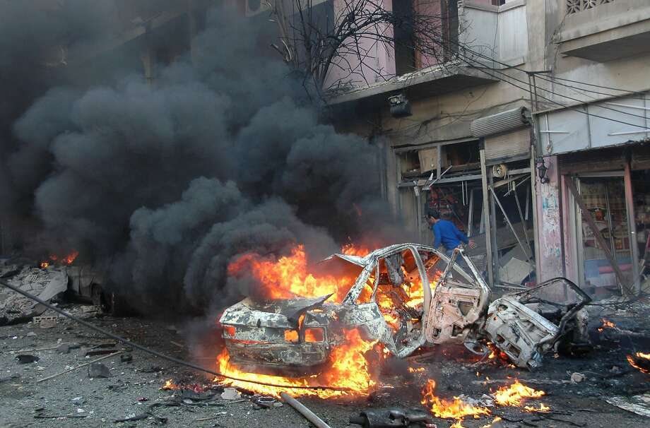 Flames engulf a vehicle following a car bomb along  al-Khudary Street in the Karm al-Loz neighborhood in the city of Homs on April 9, 2014. More than 150,000 people have been killed in Syria since the conflict began in March 2011, a monitoring group said in a new toll released. AFP PHOTO /STR-/AFP/Getty Images Photo: -, AFP/Getty Images