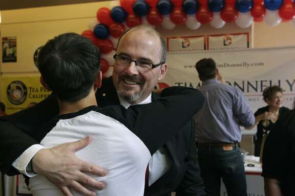 Gubernatorial candidate Tim Donnelly hugs his son Daniel at the California Republican Party spring convention in Burlingame, Calif. on Saturday, March 15, 2014.