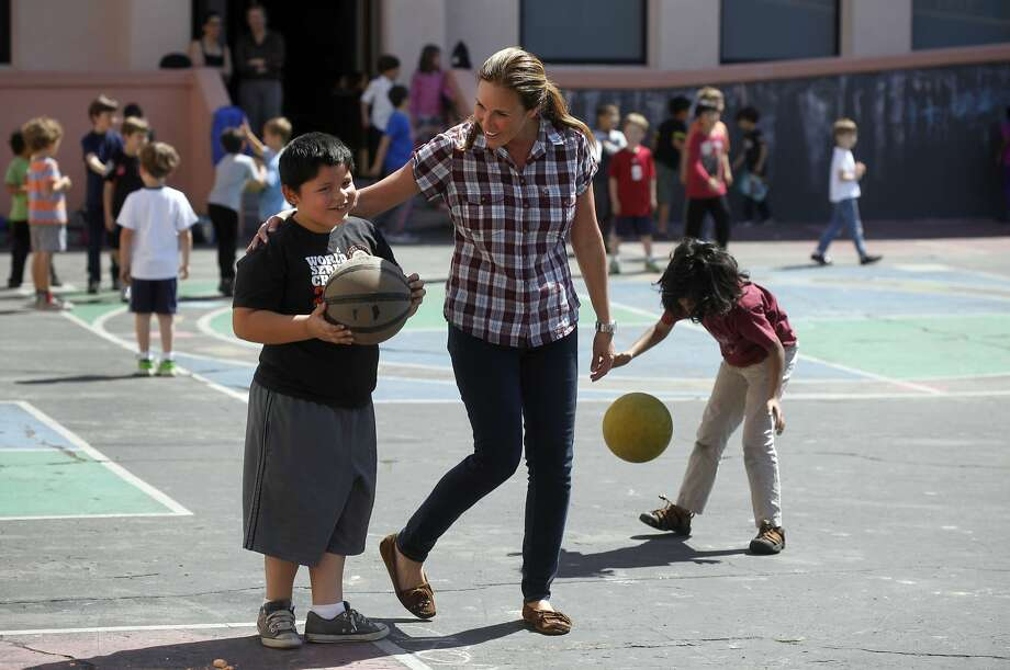 Playground monitor Betsy Gyimesi encourages Jonathan Gomez as he plays basketball at Sherman Elementary in San Francisco. Photo: Lacy Atkins, SFC