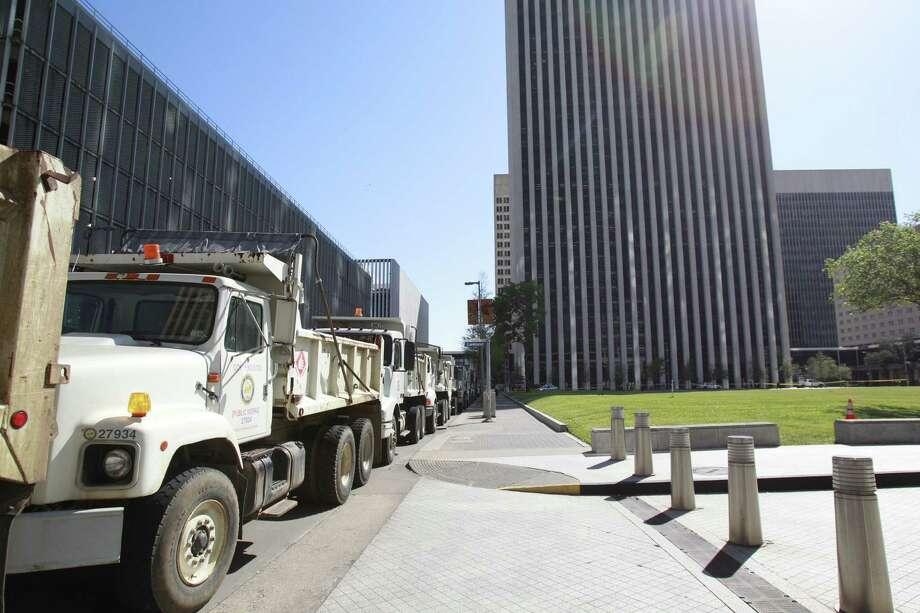 City dump trucks block open areas along Louisiana at Pease during Obama's visit to Houston. Photo: Melissa Phillip