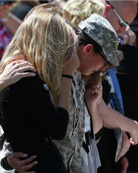 Mourners react during the III Corps and Fort Hood Memorial Ceremony, Wednesday, April 9, 2014. Sgt. First Class Daniel Michael Ferguson, Staff Sgt. Carlos Alberto Lazaney-Rodriguez and Sgt. Timothy Wayne Owens were killed and 16 others wounded when Spec. Ivan Lopez opened fire the April 2 attack at the installation. Lopez committed suicide after the attack. President Barack Obama and First Lady Michelle Obama attended the ceremony. Photo: Jerry Lara, San Antonio Express-News / ©2014 San Antonio Express-News