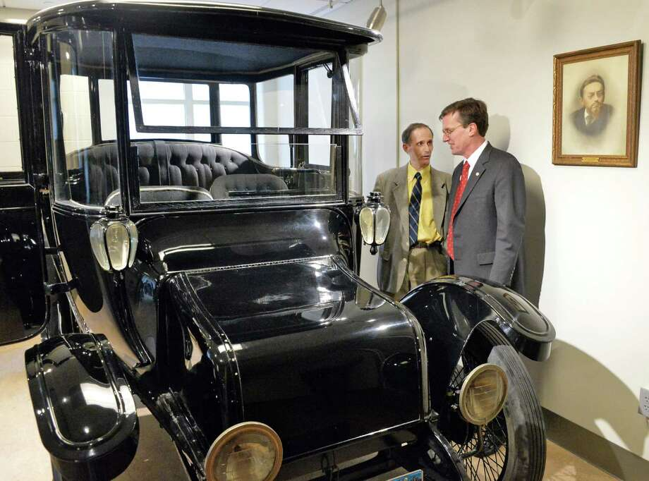 Union College President Stephen C. Ainlay, right, and engineering professor John Spinelli look over the 1914 Duplex Drive Brougham Detroit Electric automobile that belonged to Charles Steinmetz, portrait at far right, now on permanent display at the college Wednesday, April 9, 2014, in Schenectady, NY.  (John Carl D'Annibale / Times Union) Photo: John Carl D'Annibale / 00026424A