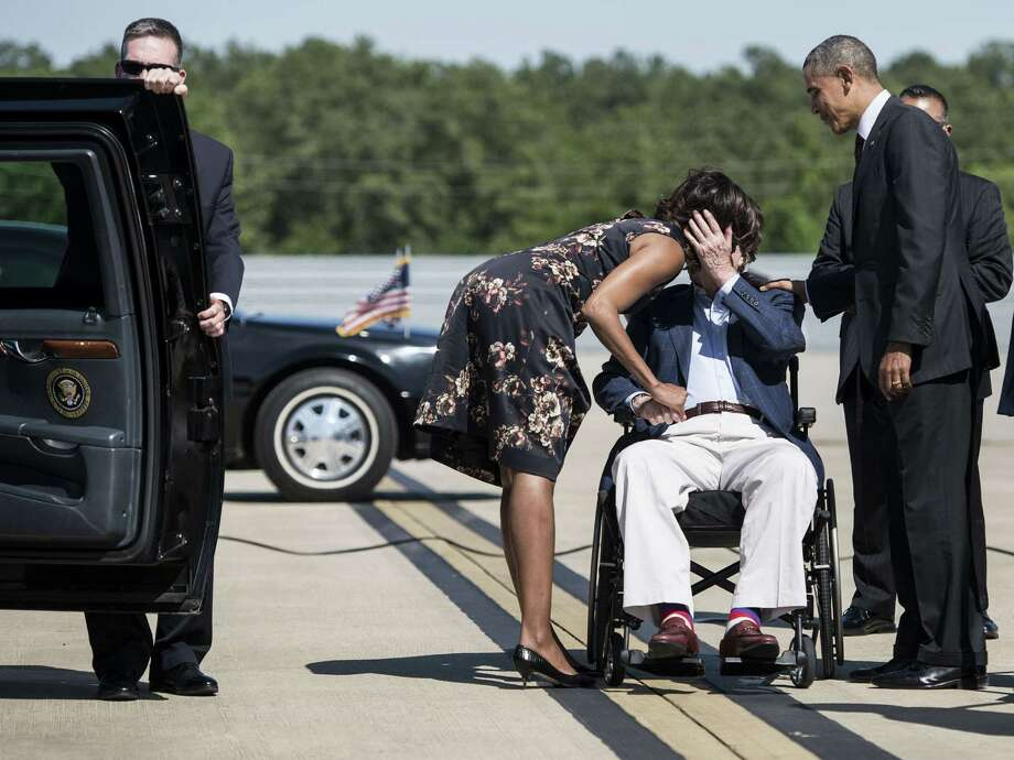 Former US President George H. W. Bush greets US President Barack Obama and First Lady Michelle Obama as they arrive at Intercontinental Airport on April 9, 2014 in Houston, Texas. Obama, who attended a memorial service at Fort Hood, is in Houston to attend two fund raisers for the Democratic National Committee, the Democratic Congressional Campaign Committee and the Democratic Senatorial Campaign Committee.  AFP PHOTO/Brendan SMIALOWSKIBRENDAN SMIALOWSKI/AFP/Getty Images Photo: BRENDAN SMIALOWSKI, AFP/Getty Images / 2014 Brendan Smialowski