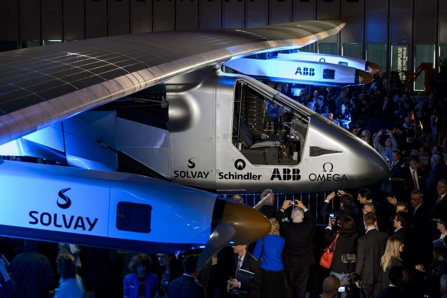 People look at the second Solar Impulse 2 solar-powered plane to be used for a round-the-world voyage next year, during its unveiling in Switzerland on April 9, 2014. Photo: FABRICE COFFRINI, AFP/Getty Images