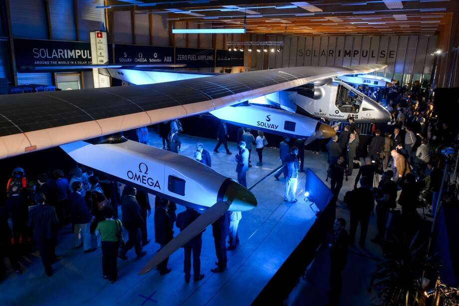 People look at the Solar Impulse 2 solar-powered plane to be used for a round-the-world voyage, during its unveiling in Switzerland on April 9, 2014. Photo: FABRICE COFFRINI, AFP/Getty Images